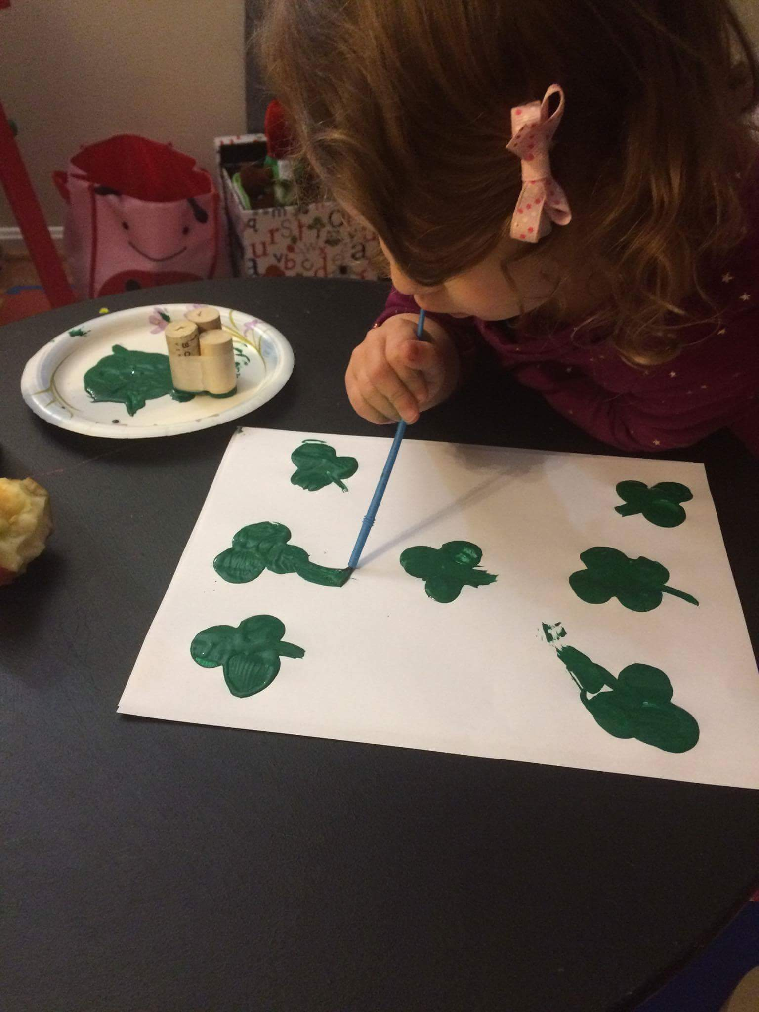 G painting stems on the shamrocks